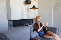 La femme blonde tient le téléphone portable et mange la fraise mûre, se reposant Photos stock