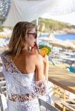 La femme blonde a un cocktail à une barre de plage pendant l'heure d'été photos stock