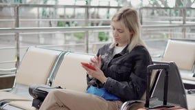 La femme blonde utilise le smartphone dans le refuge dans l'aéroport ou la gare ferroviaire banque de vidéos