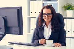 La femme boit du café dans le bureau photos stock