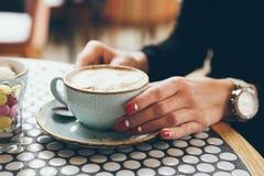 La femme boit du café dans un café moderne Photographie stock libre de droits