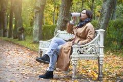 La femme boit du café sur le banc en parc de feuilles de jaune d'automne photos stock