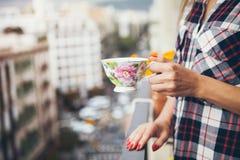 La femme boit du café sur un balcon avec la grande vue de ville Photos libres de droits