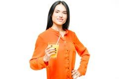 La femme boit du jus d'orange, fond blanc photographie stock