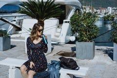 La femme boit du thé ou du café de la tasse thermo sur la rue, l'Europe image stock