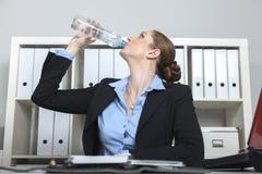 La femme boit l'eau dans le bureau Image stock
