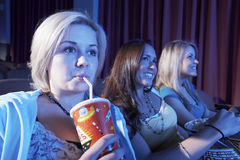 La femme boit la boisson non alcoolisée avec des amis observant le film dans le théâtre Image stock