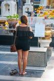 La femme bouddhiste prie, près du grand centre commercial, Bangkok Photo stock
