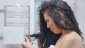 La femme bouleversée regarde les cheveux endommagés banque de vidéos