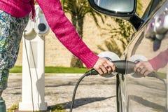 La femme branche la voiture électrique à la station de charge Image libre de droits