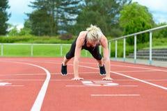 La femme célibataire étirant le veau muscles à la voie de course photographie stock libre de droits