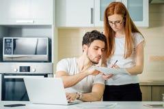 La femme calculent ou écrivent des comptes avec le stylo, son mari à l'aide de l'ordinateur portable images libres de droits
