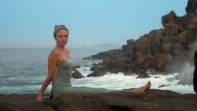 La femme calme dans le gris s'assied sur le mouvement lent de côte rocheuse d'océan clips vidéos