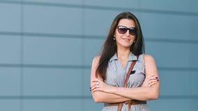 La femme calme de sourire dans des lunettes de soleil se tenant avec des bras a croisé dans le mur de fond du bâtiment moderne banque de vidéos