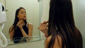 La femme caresse sa peau dans la salle de bains Photo stock