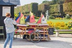 La femme casse la photo des voiliers de jouet sur le chariot au jardin du Luxembourg, Photos stock