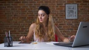 La femme caucasienne attentive magnifique dactylographie sur l'ordinateur portable et frappe à toute volée son comprimé dans l'in clips vidéos