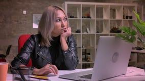 La femme caucasienne blonde futée s'assied sur le lieu de travail et considère tout en regardant au-dessus de son ordinateur, tra banque de vidéos