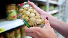 La femme caucasienne de plan rapproché remet près des étagères de boutique choisissant des champignons de marinade sur le marché  clips vidéos