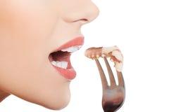 La femme caucasienne de sourire mangeant la mer portent des fruits avec la fourchette. images stock