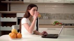 La femme cause heureusement sur l'ordinateur portable clips vidéos