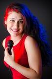 La femme chantant dans le club de karaoke Photos stock