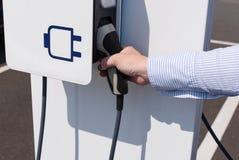 La femme charge son véhicule électrique d'un câble de remplissage photographie stock
