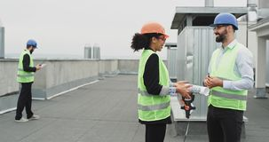 La femme charismatique même et l'ingénieur bel ont une conversation sur le dessus de toit du site de construction de bâtiments banque de vidéos