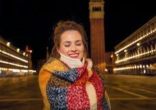 La femme chez Piazza San Marco tenant le St proche marque le campanile photo libre de droits