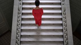 La femme chic dans la longue robe rouge sur des talons hauts monte un grand escalier et regarde sur l'appareil-photo banque de vidéos