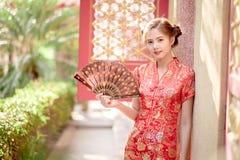 La femme chinoise asiatique dans la prise de chinois traditionnel éventant la PA Image stock