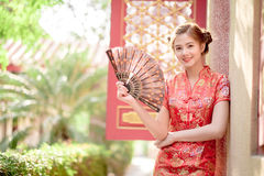 La femme chinoise asiatique dans la prise de chinois traditionnel éventant la PA images stock