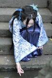 La femme chinoise dans la robe bleue et blanche traditionnelle de Hanfu s'asseyent sur les étapes et la palette Photos libres de droits