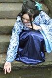 La femme chinoise dans la robe bleue et blanche traditionnelle de Hanfu s'asseyent sur les étapes et la palette Image libre de droits