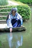 La femme chinoise dans la robe bleue et blanche traditionnelle de Hanfu s'asseyent sur les étapes et la palette Photo stock
