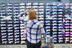 La femme choisit des espadrilles dans le magasin d'habillement de sport Photos stock