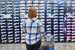 La femme choisit des espadrilles dans le magasin d'habillement de sport Image libre de droits