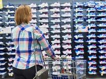 La femme choisit des espadrilles dans le magasin d'habillement de sport Photos libres de droits