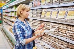 La femme choisit des oeufs d'emballage dans le supermarché Photographie stock libre de droits