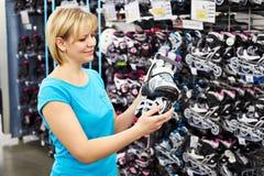 La femme choisit des patins de rouleau dans la boutique de sports Photographie stock libre de droits