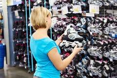 La femme choisit des patins de rouleau dans la boutique de sports Photo stock