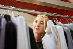 La femme choisit des vêtements dans le magasin Photo stock
