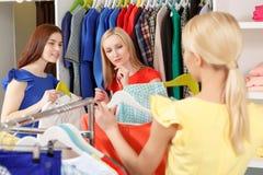 La femme choisit des vêtements dans un magasin Images stock