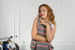 La femme choisit des vêtements dans un magasin d'habillement photographie stock libre de droits