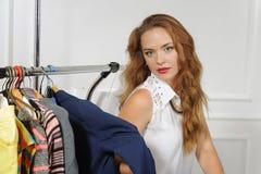 La femme choisit des vêtements dans un magasin d'habillement Photo stock