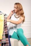 La femme choisit des vêtements dans une boutique Photo stock