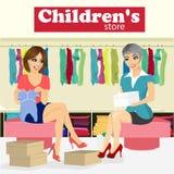 La femme choisit des vêtements de bébé pour son amie enceinte dans le magasin des enfants avec l'aide de l'assistant de magasin Photographie stock libre de droits