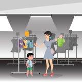 La femme choisit des vêtements pour son fils dans la boutique Photo stock