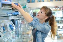 La femme choisit l'appareil électronique dans le magasin photo stock