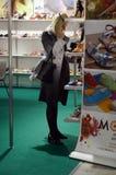 La femme choisit l'exposition spécialisée par International à la mode de chaussures de chaussures pour des chaussures, des sacs e Photos libres de droits